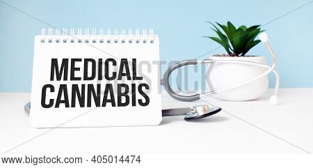 The Text Medical Cannabis Is Written On Notepad Near A Stethoscope On A Blue Background. Medical Con