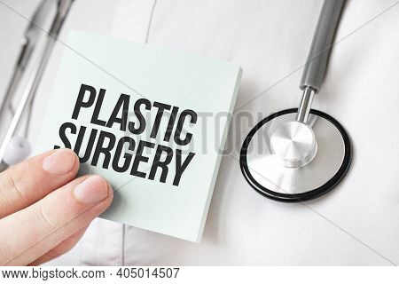 Doctor Holding Card In Hands And Pointing The Word Plastic Surgery