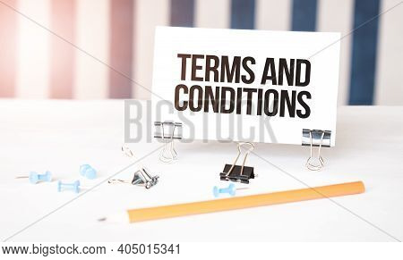 Terms And Conditions Sign On Paper On White Desk With Office Tools. Blue And White Background