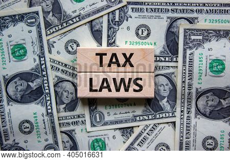 Tax Laws Symbol. Concept Words 'tax Laws' On Wooden Blocks On A Beautiful Background From Dollar Bil