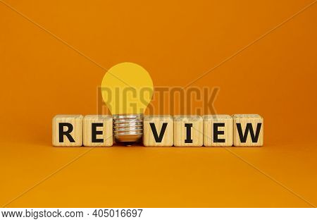 Review Symbol. Wooden Cubes With Word 'review'. Yellow Light Bulb. Beautiful Orange Background. Busi