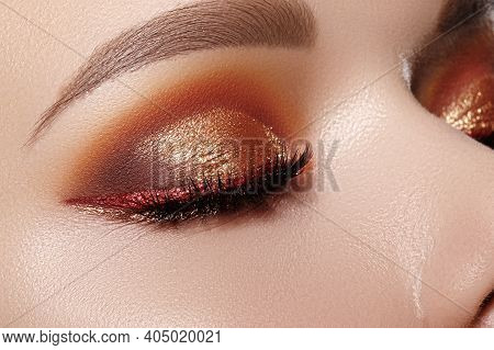 Closeup Macro Of Woman Face With Gold Glitter Eyes Make-up, Bright Red Liner. Fashion Celebrate Make