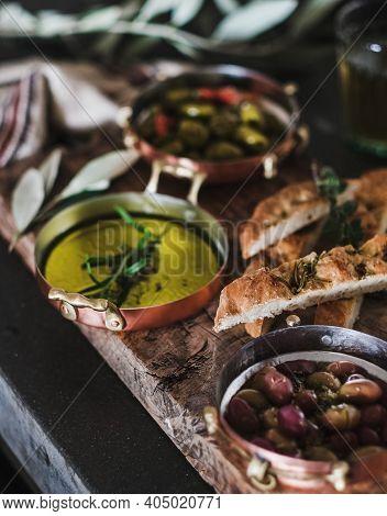 Pickled Greek Olives, Olive Oil In Copper Jars And Herbed Focaccia Slices On Rustic Wooden Board, Se