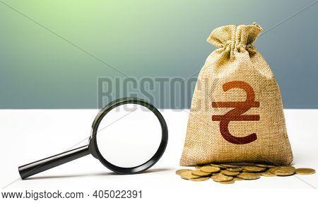 Ukrainian Hryvnia Money Bag And Magnifying Glass. Origin Of Capital Funds. Revising The Budget To Sa