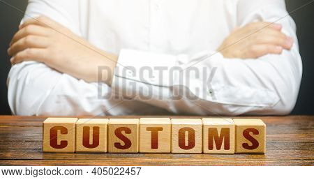 Man With Folded Hands On His Torso And Blocks With Word Customs. Customs Border Control. Tariffs And