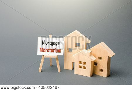 Houses Figures And An Easel Sign With Mortgage Moratorium. Moratorium On Loan Repayments. Financial