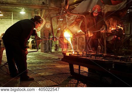 Steel workers melting iron in furnace steel mill