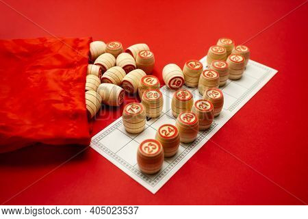 Wooden Bingo Kegs, On A Red Background In A Red Bag, For Playing Bingo. A Way To Spend Time At Home.