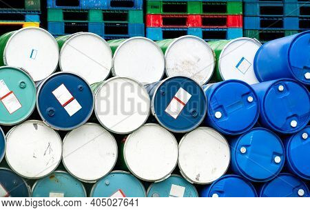 Old Chemical Barrels In Front Of Stacked Plastic Pallet At The Factory. Blue And Green Oil Drum. Ste