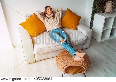 Calm Satisfied Woman Relaxing Or Sleeping On The Sofa In Living Room. Carefree Lady Resting At Home,