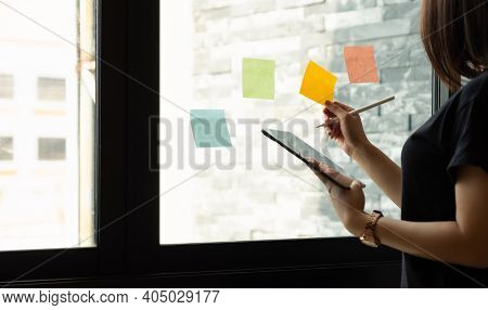 Business Woman Using Tablet During Post It Notes Idea Discussing And Planning In Glass Wall At Meeti