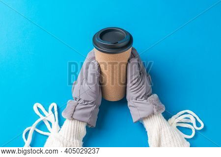 Hands Of A Girl In A White Sweater And Mittens With A Paper Cup Of Coffee On A Blue Background. Hot