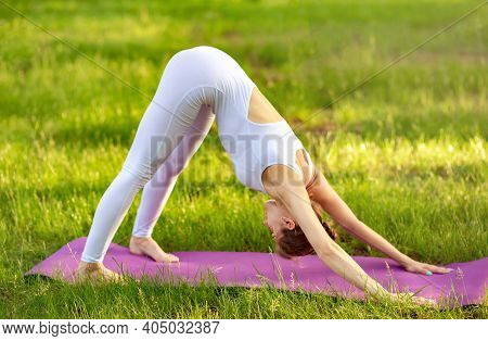 Sporty Young Woman Doing Yoga At Park In The Morning. Female Workout On Yoga Mat. Adult Woman Practi