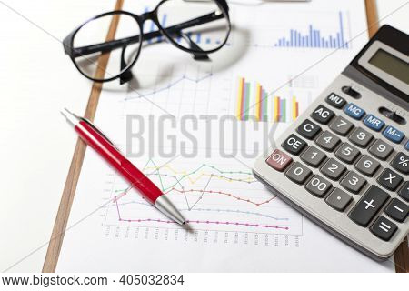 Finance And Business Concept. Calculator On Financial Graphs On Desk. Accounting Budgeting Loans Or