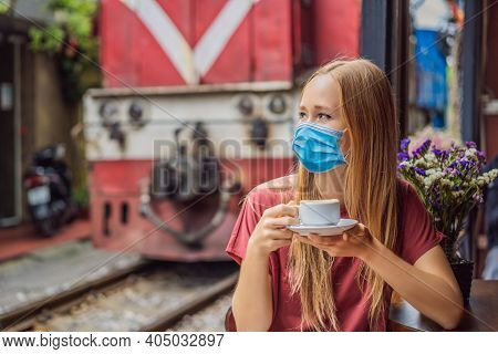 Young Woman Traveler Wearing A Medical Mask During Covid-19 Coronavirus Drinks Vietnamese Coffee Wit