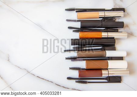 Flat Lay Of Composition Of Mascara Brushes, Mascara For Eyelash And Eyebrow On White Marble Table.
