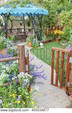 Lush Landscaped Backyard Flower Garden With Wooden Gate