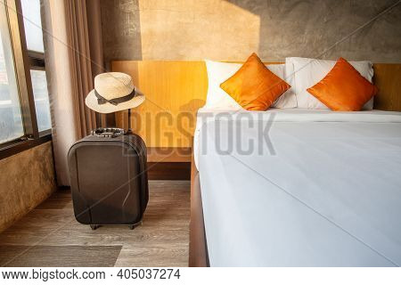 A Suitcase With Hat In Comfortable Hotel Bedroom In Cozy Style. Conceptual Of Travel And Accommodati