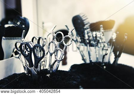 Close-up Of Scissors And Brushes In A Stand. Beauty Salon Tools. Selective Soft Focus. Lens Glare