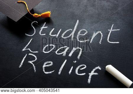 Student Loan Relief Written On The Blackboard And Graduation Cap.