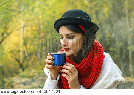 A Woman In A White Coat, Crochet Red Scarf And Black Hat Holds A Cup In Her Hands. Tea Party In Natu