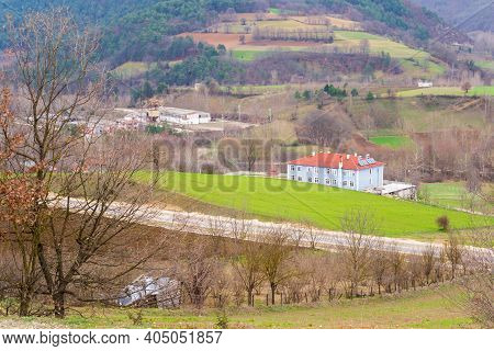 Scenic View Of Mountainous Valley With Country Houses And Bright Green Spring Grass Surrounded With