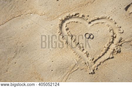 A Wedding Ring On The Sand And They Are Wedding Rings.