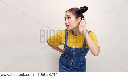 Eavesdropping Concept. Asian Girl Holding Her Hand Near Ear And Listening Carefully Isolated Over Wh