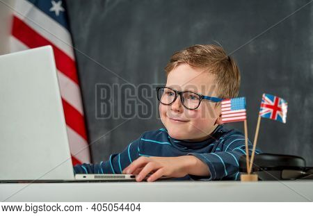 Back To School. Cute And Happy Little Kid Boy Has Lesson On Laptop. English On Computer. Seven Years