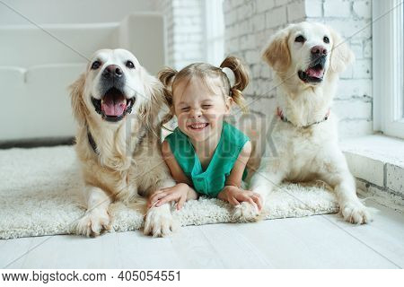 Happy Child With A Dog. Portrait Of A Girl With A Pet. Labrador Retriever At Home. . High Quality Ph