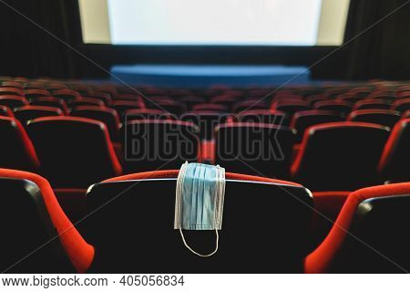 A Medical Mask Hangs On A Chair In An Empty Cinema Hall. Pandemic And Crisis In The Industry. Delaye