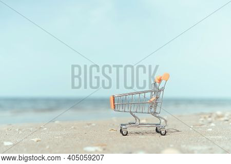 Shopping Basket Cart On Sand Beach With Blue Sky Background. Summer Sale And Business Service Concep