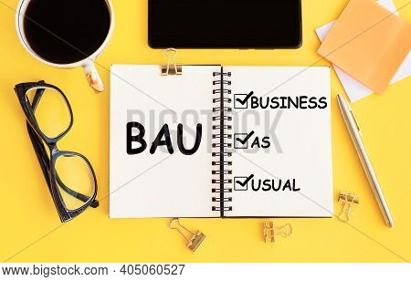 Acronym Bau - Business As Usual. Text On Notepad And Office Accessories On Yellow Desk.