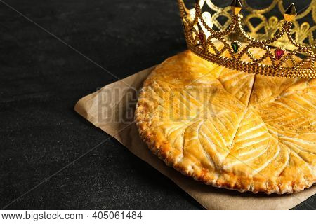 Traditional Galette Des Rois With Decorative Crown On Black Table