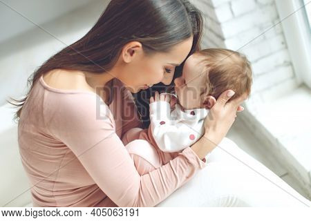 A Loving Mother Caring For Her Newborn Baby At Home. Bright Portrait Of A Happy Mother Holding A Sle