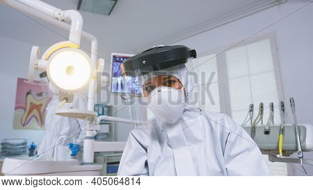 Patient Pov Of Dentist Explaining Teeth Treatment Wearing Covid Protective Suit In New Normal Stomat