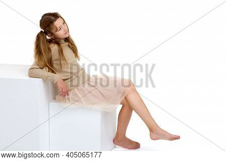 Beautiful Preteen Girl Sitting On A White Cube In Studio. Cute Barefoot Girl With Pigtails Wearing K