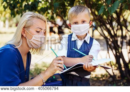 Mom Tells Her Son What Awaits Him At School. They Hold A Notebook In Their Hands And Make Notes. The