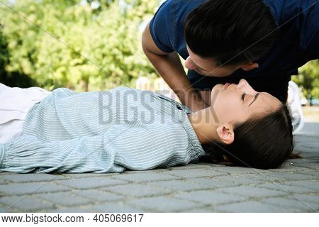 Man Checking For Breathing Of Unconscious Young Woman Outdoors