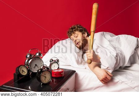 Dreams. Man Wakes Up At His Bed On Red Background And Hes Mad At Clocks Ringing, Switches It Off Wit