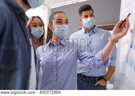 Group Of Coworkers With Protective Masks Near Whiteboard In Office. Business Presentation During Cov