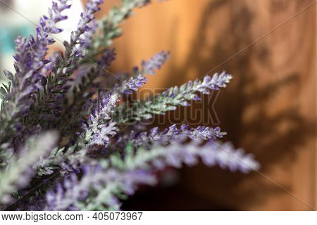 Artificial Heather Lavender Flowers Bouquet And Shadow On Wooden Wall, Home Interior, Selective Focu