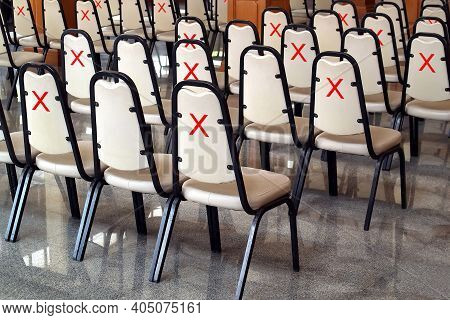 Red Cross Marks Tape Paste On Back Of White Leather Chairs In Empty Seminar Hall (meeting Room), Sit