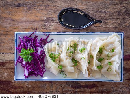 Top View Of Fresh Chinese Dumplings Or Jiaozi On A Plate. Chinese Food With Hot Steams On An Old Woo