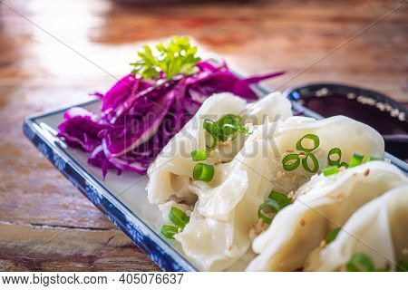 Side View Of Fresh Chinese Dumplings Or Jiaozi On A Plate On Old Wooden Table. Selective Focus. Chin