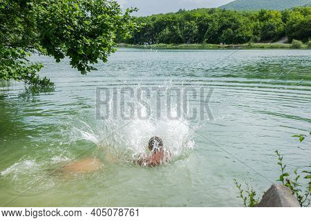 Happy Children Swim In The Lake In The Summer. The Concept Of Summer Holidays, Weekends, Holidays. A