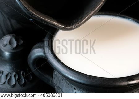 Fresh Pasteurized Cow's Milk In A Bowl Of Black Clay On A Black Background Close-up Macro Photograph
