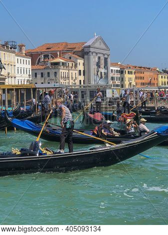 August 2018 Venice, Italy: Gondoliers In Boats With Tourists Across Buildings, Sea And Blue Sky