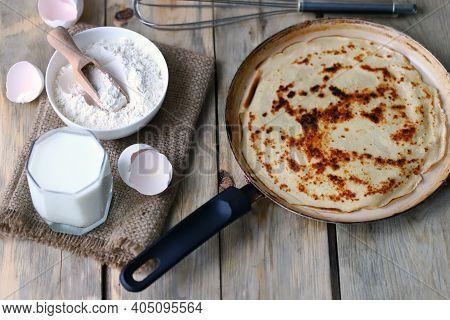 Frying Pan With Pancake, Flour, Milk, Eggs. Pancake Making Concept. Maslenitsa Celebration.