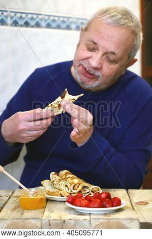 Cheerful Man With Pancakes. The Man Happily Eats Pancakes. Pancake Week.